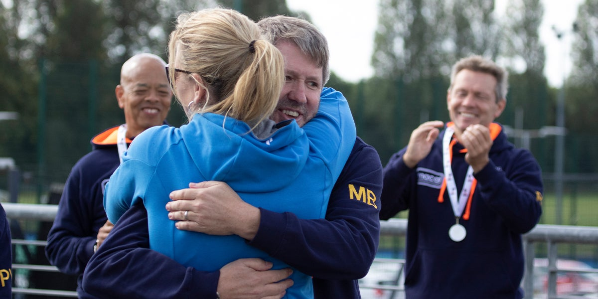 Hockey player hugging his manager after presenting medals at the England Hockey Championships.