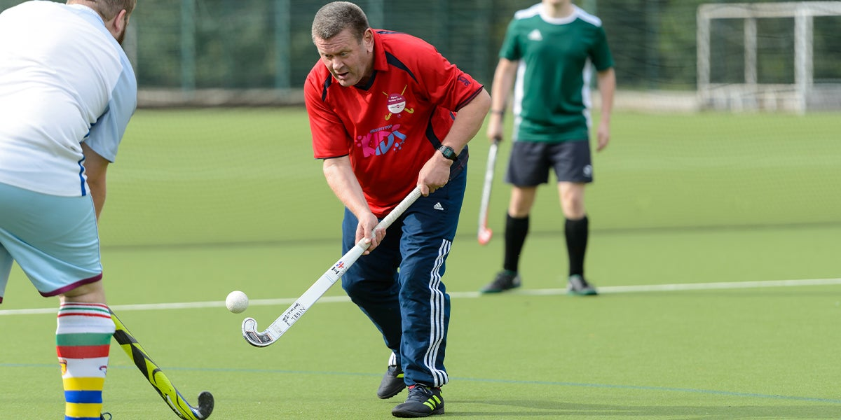 Adult male playing hockey on a green pitch