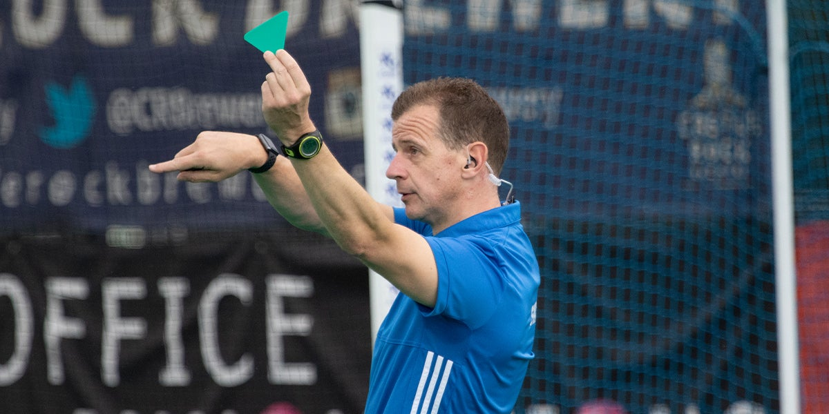 Hockey umpire issuing a green card