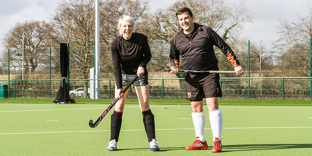Male and female playing hockey on a green pitch