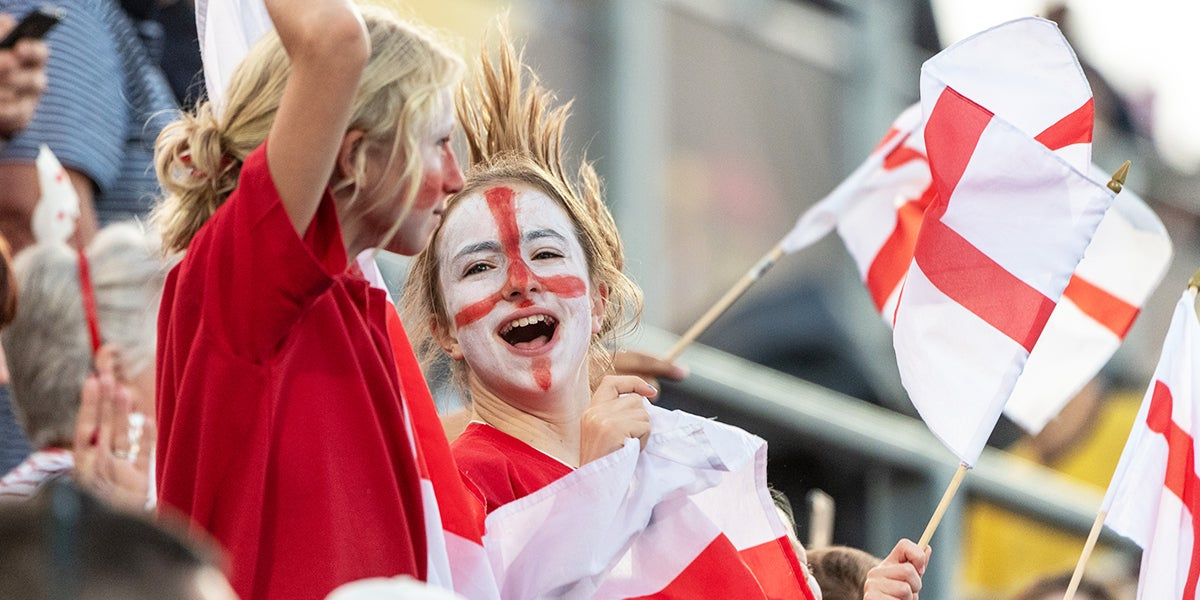 Girls waving England Flags at Hockey Event