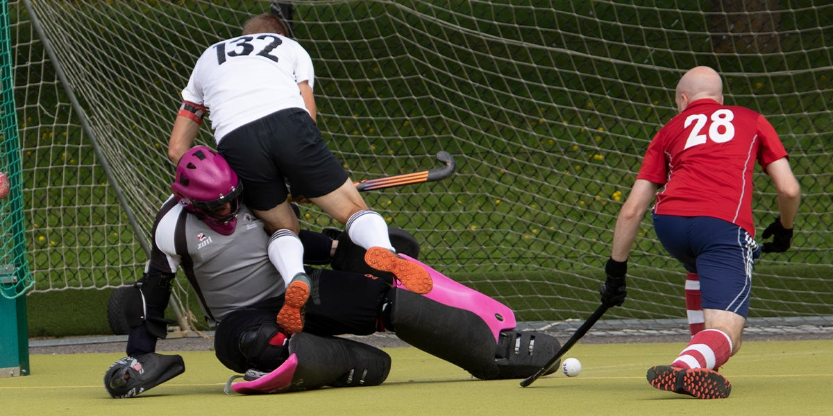 Newbury and Thatcham Hockey Club Goalie making a save and wiping out a player