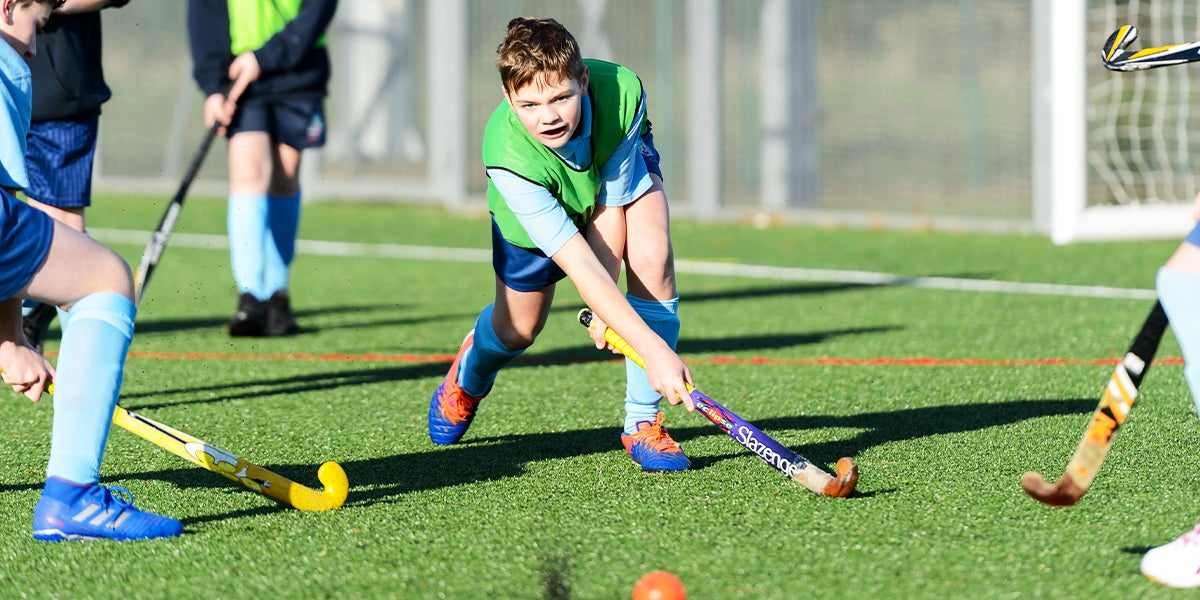 Young boy playing hockey on a green pitch