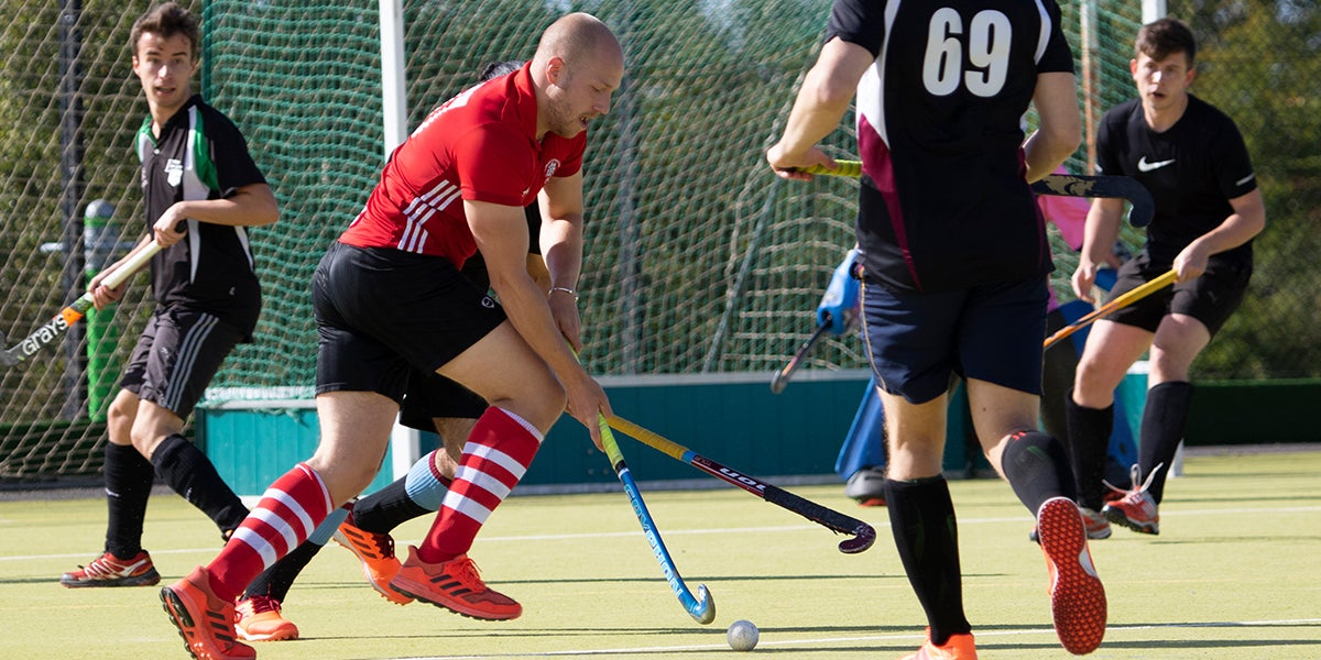 Male hockey players playing on a green pitch
