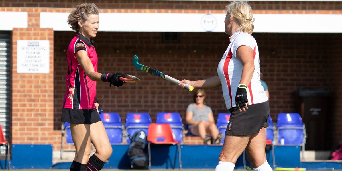 Adult Female hockey players tapping sticks during COVID-19 at England Hockey Championships 2019-20