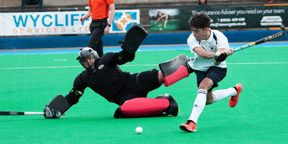 Goalie makes a diving save to stop a shot at the England Hockey Championships