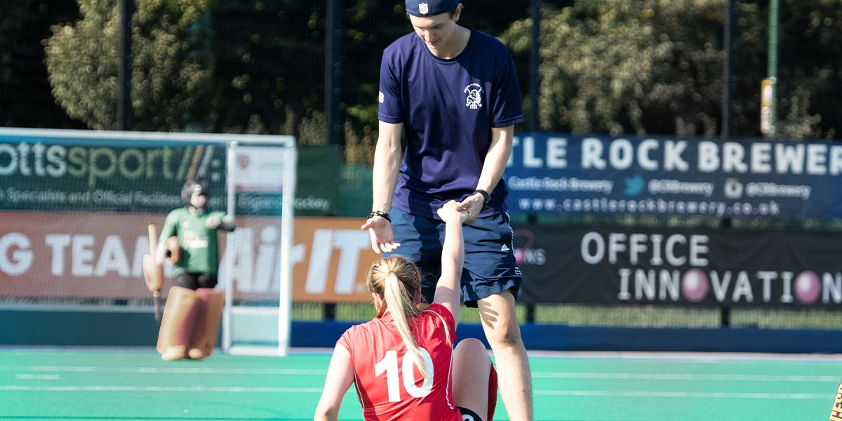 Player being helped off the ground at the England Hockey Championships