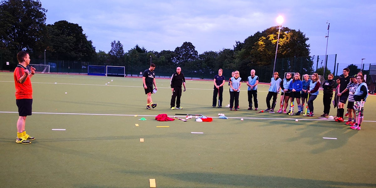 Coach delivering a hockey session to adults on a green pitch