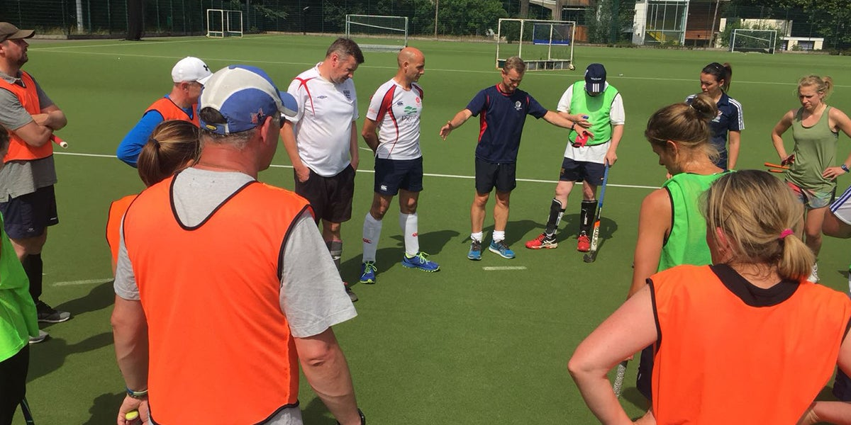 Coach delivering a hockey session on a green pitch to adults