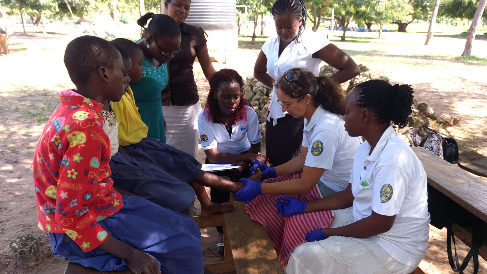 Treating a child's foot for tungiasis.