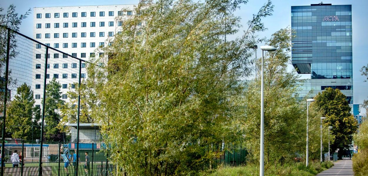 Het ACTA-gebouw gezien vanuit het oosten, met het fietspad en de sportvelden op de voorgrond.